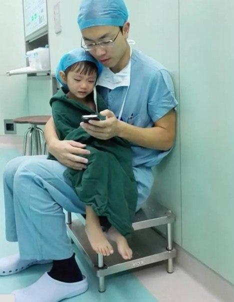 Хирург утешает плачущую девочку перед операцией, смотря с ней мультики