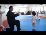 Маленький мальчик пытается разбить дощечку на Тхэквондо