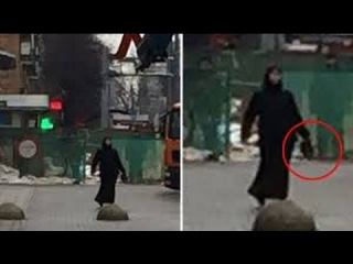 Woman in black holding severed child's head Moscow