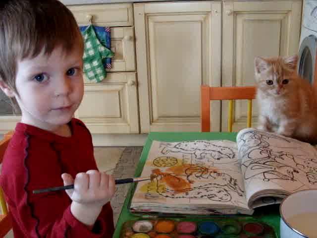 Ребенок рисует с кошкой
