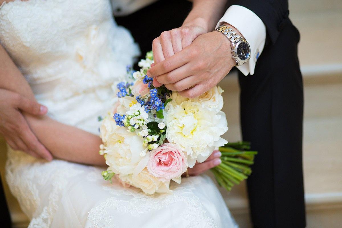 руки жениха и невесты с букетом