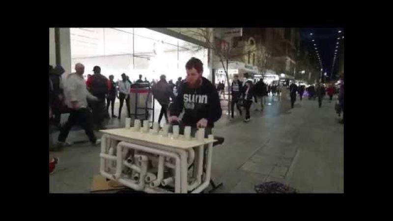 Парень играет техно на пластиковых трубах
