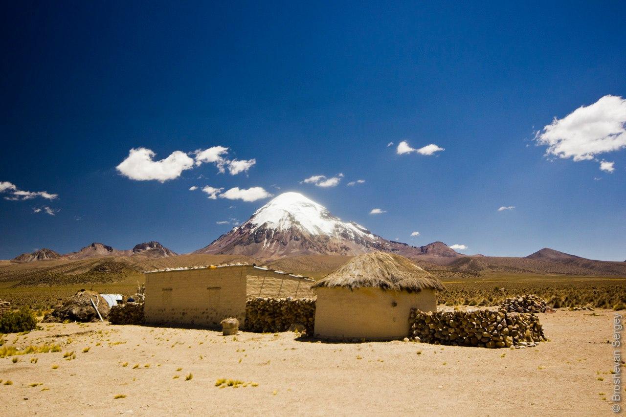 Глиняные домики на фоне вулкана Сахама