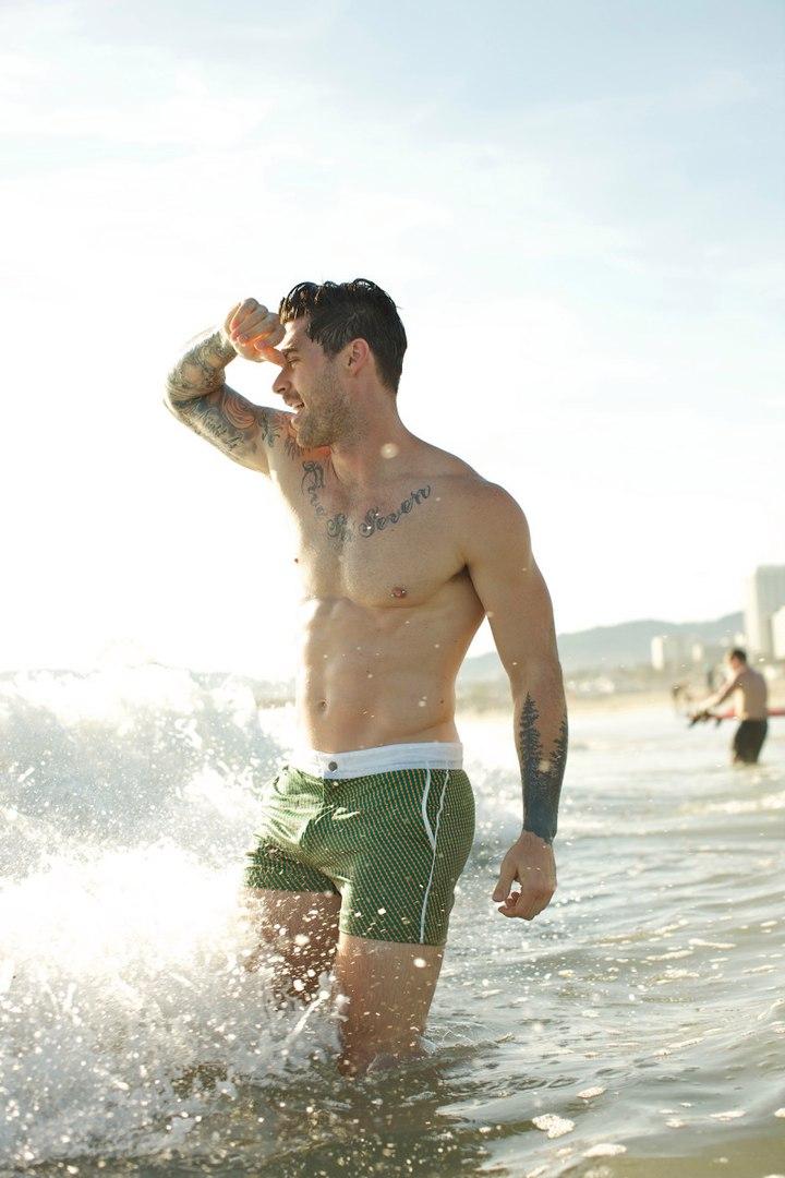 Майже голий хлопець на пляжі. Фото