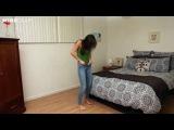 Симпатичная девушка пытается надеть очень узкие джинсы