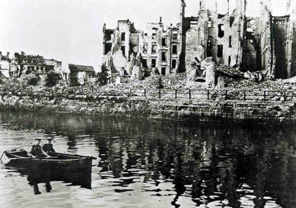 Советские офицеры плывут на лодке по реке