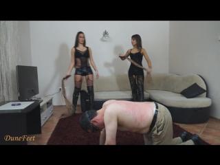 Две сексуальные Госпожи флогерами стегают раба по спине.