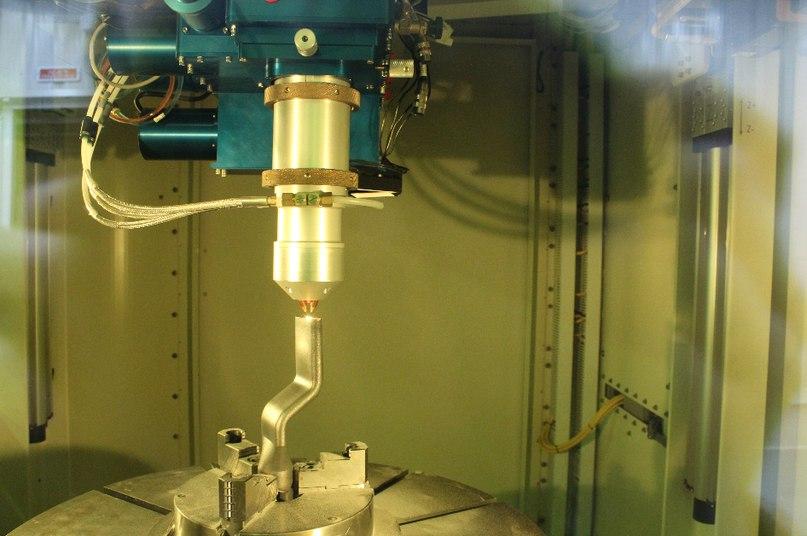 Лазер спекает новый слой металлического порошка