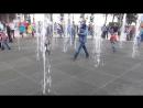 Девочки и мальчики балуют в фонтанчике