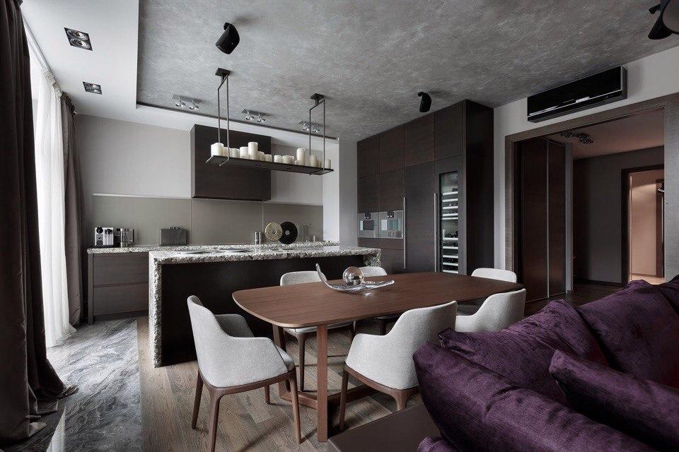 Визуальное разграничение зоны приготовления, питания и отдыха мебелью является частым приемом в интерьерах кухонь, совмещенных с гостиной.