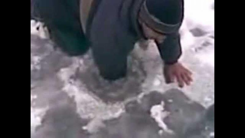 Рыбак достает огромную щуку из лунки на зимней рыбалке