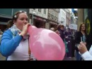Chubby girl blows to pop a red balloon outside