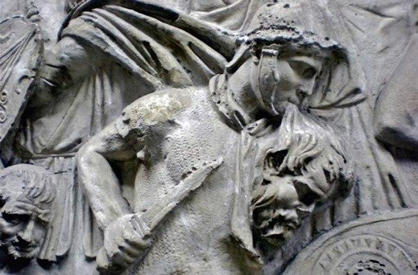 Колонна Трояна. Римский ауксилиарий держит в зубах отрубленную голову врага