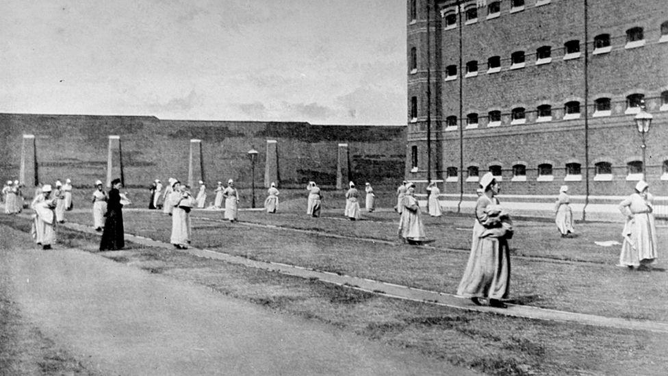 Women walk with their children in the pleasure yard of Wormwood-Scrubs prison, 1890.