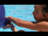 Girl blow to pop big blue balloon in a pool