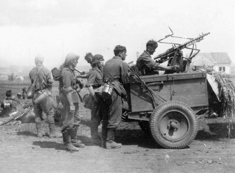 Немецкие солдаты у 7,92 мм зенитной установки Zwillingssockel-36 в населенном пункте, во время привала в ходе марша.