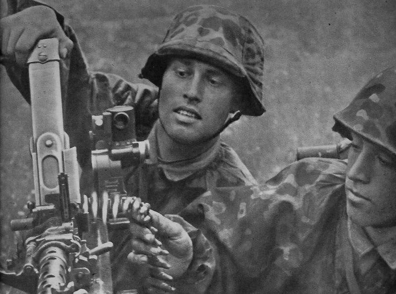 Немецкие солдаты из состава войск СС перезаряжают пулемет MG-34.