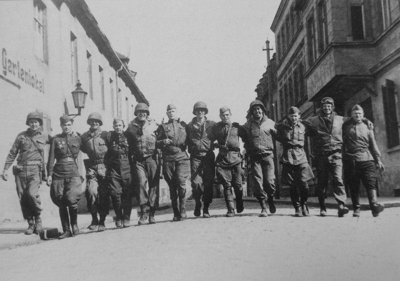 Солдаты 58-й гвардейской стрелковой дивизии и американской 69-й пехотной дивизии (69th Infantry Division) идут, обнявшись за плечи, по улице Торгау. 1945 год.
