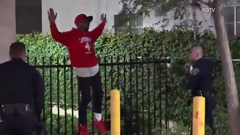 Bystander_ Man Gets His Jeans Stuck On Fence As He Surrenders To Police