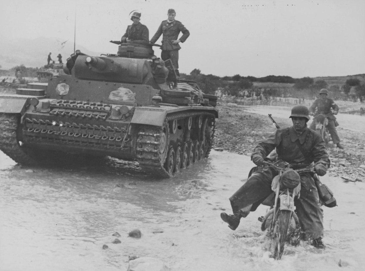 Мотоциклист Африканского корпуса вермахта и танк Pz.Kpfw. III форсируют реку Оуед Маароуф в Тунисе. 1943 г.