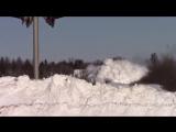 Товарный поезд разрывает снежные глыбы