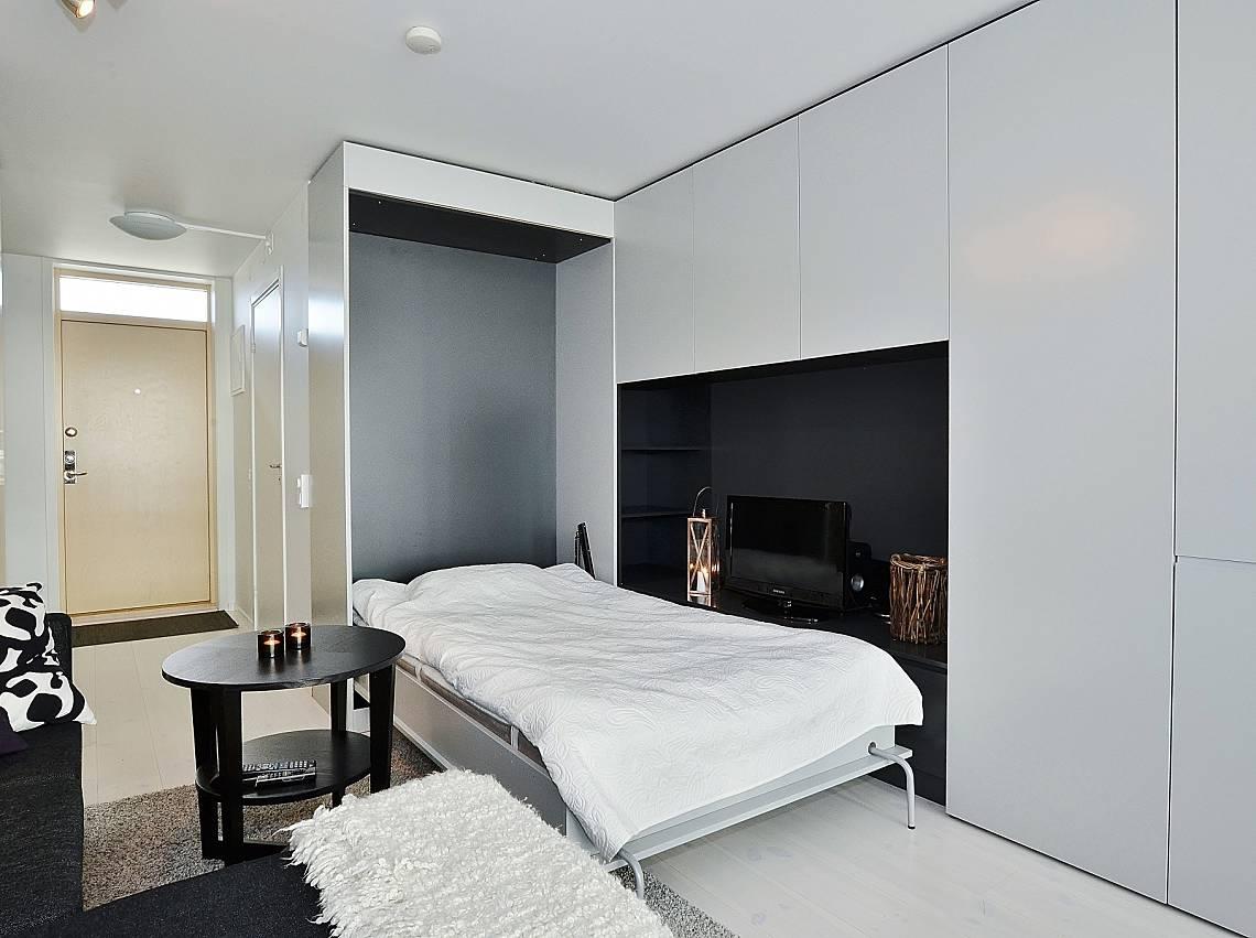 Интерьер квартиры-студии 32 м с кухней у окна и откидной кроватью.