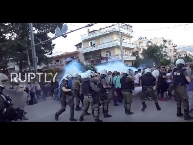 Греция: Полицейские демонстранты, бросающие камни, требуют выселения Ромы.
