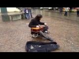 Уличный музыкант играет на гитаре флягой. Талант