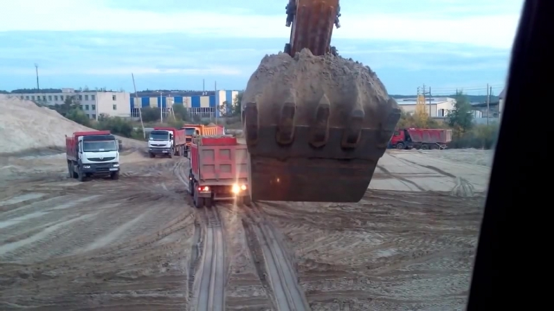 Погрузка песка на площадке вид с эскаватора