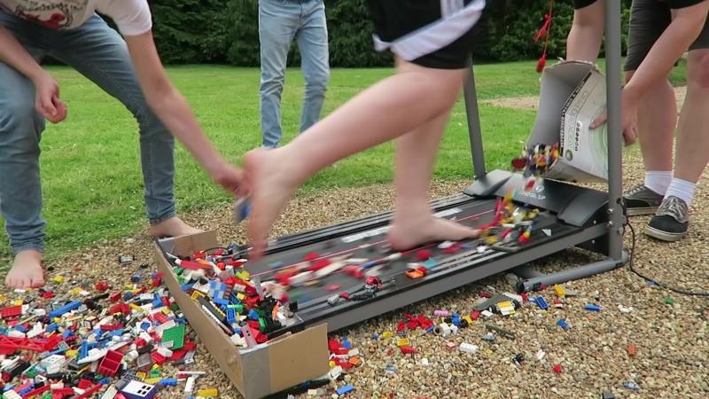 Отчаянные парни бегут по беговой дорожке босыми ногами по деталям LEGO.