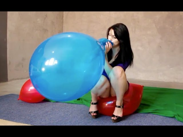 Girl blow and sit to pop balloons