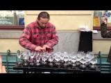 Талантливый уличный музыкант играет на стеклянных стаканах