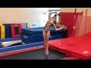 Девочка гимнастка делает сальто.