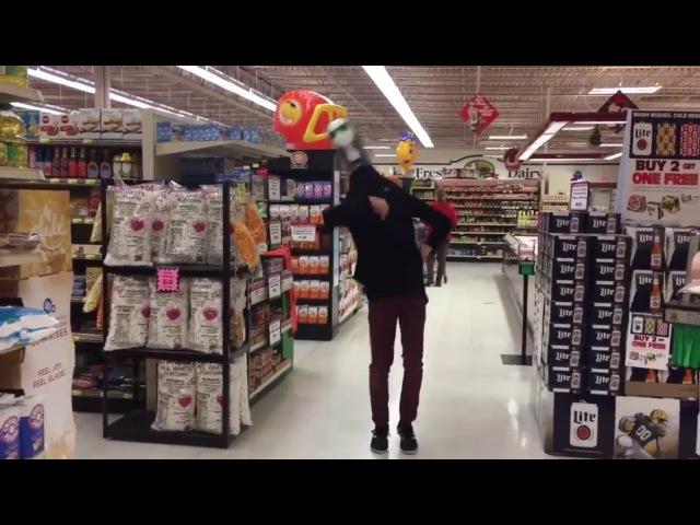 Парень круто танцует с головой манекена на голове в магазине