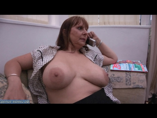 Зрелая женщина с большой грудью разговаривает по телефону на счет секса втроем