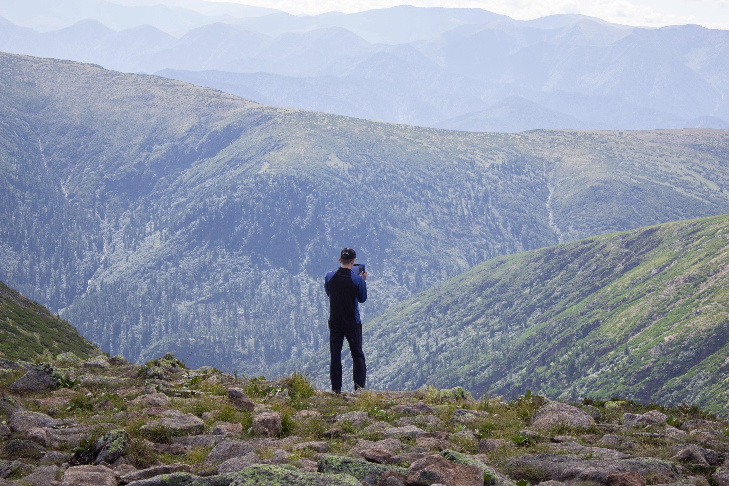 Антон фотографирует виды с вершины перед спуском