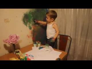 Мальчик рисует на обоях.