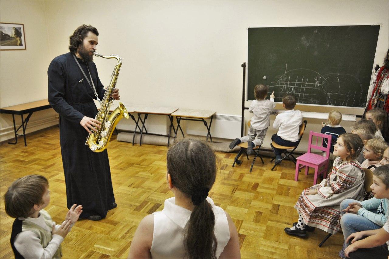 о. Герман играет на саксофоне для детей