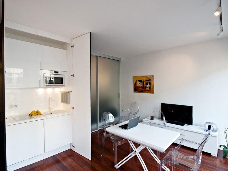 Интерьер квартиры 30 м в Париже с кухней в шкафу и раздвижными перегородками из матового стекла.