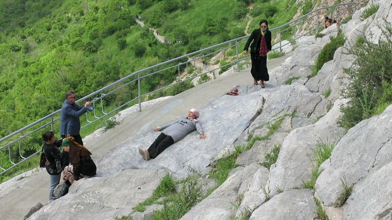 Ош, гора Сулеймана. Женщины катаются с каменной горки)