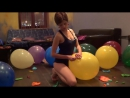 Beautiful girl sit to pop big balloons