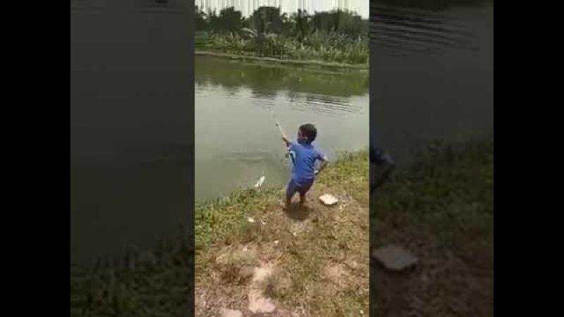 Маленький рыбак поймал на удочку рыбу размером с самого с себя