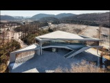 Moveable wooden screens are set into concrete facades of Mokyeonri Wood Culture Museum
