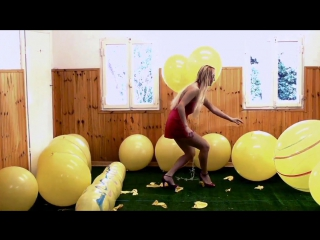 Girl bursting big yellow balloons