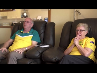 Дедушка и бабушка смотрят как внук выигрывает золотую медаль на Олимпиаде