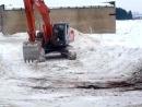 Экскаватор чистит дорогу от снега бревном