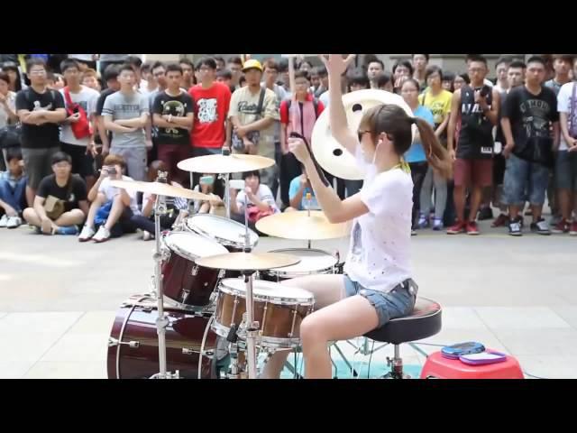 Девушка играет на барабанах артистичный перформанс