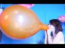 Girl blow to pop big orange balloon