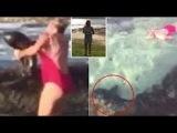 Woman wrestles shark in rock pool.