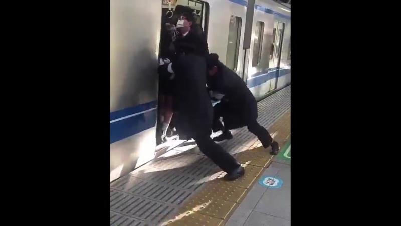 Трое железнодорожных сотрудников заталкивают пассажиров в поезд